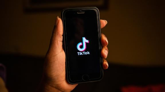 New York, United States, 6th January 2021: A woman holds a phone with the TIKTOK logo in her hand. It's one of the most popular social networks at the moment.