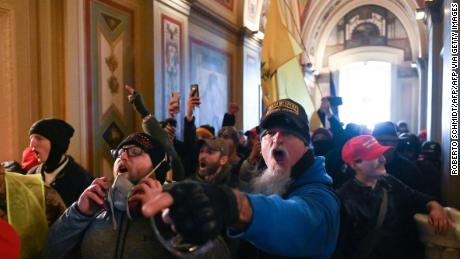A man wearing an Oath Keepers hat shouts in the Capitol corridors during the January 6 invasion of rebels.