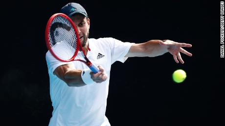Karatsev plays a forehand against Dimitrov.
