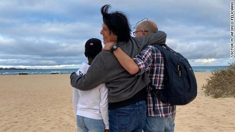 Abou, left, from Ivory Coast, is pictured with his foster parents Deli Delgado and Victor Afonso at Corralejo beach, an area where many boats land when they arrive in the Canary Islands from West Africa.