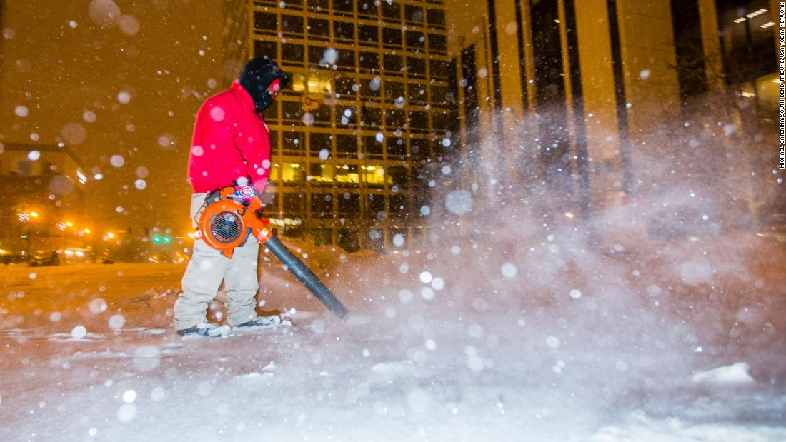 A city employee clears sidewalks in South Bend, Indiana, on Monday.