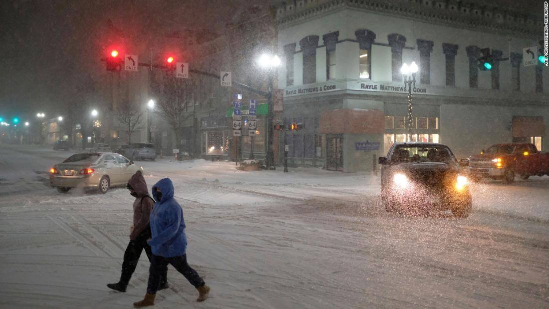 Two women cross Main Street as snow falls in Bowling Green, Ohio, on Monday.