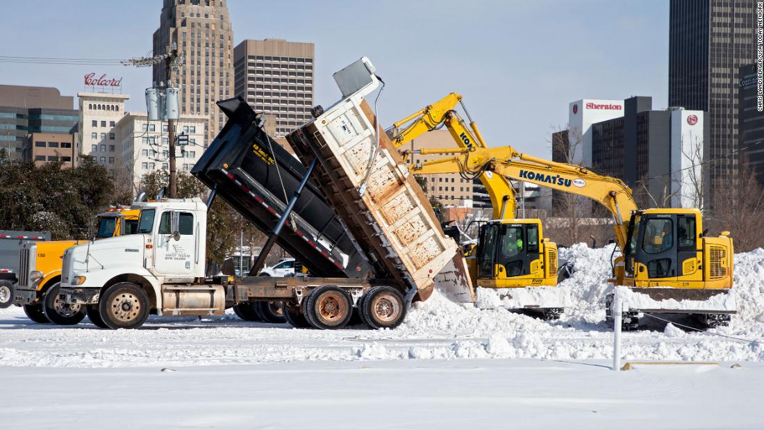 Crews unload snow that they removed from city streets in Oklahoma City.