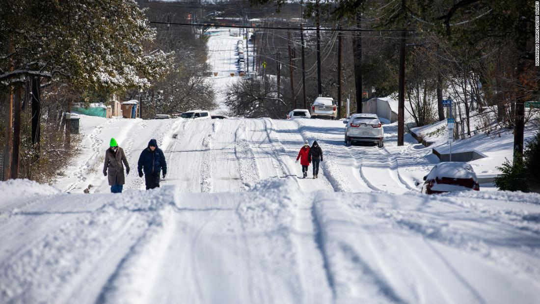 People walk on a snowy road in Austin, Texas, on Monday.