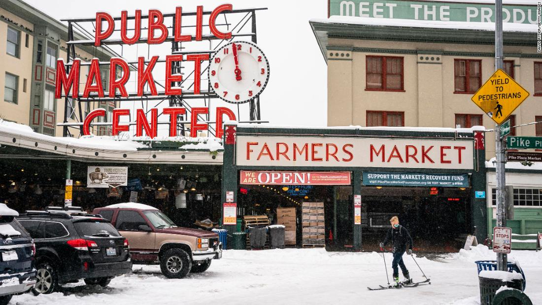 Harrison Walsh skis by Seattle's Pike Place Market on Saturday.