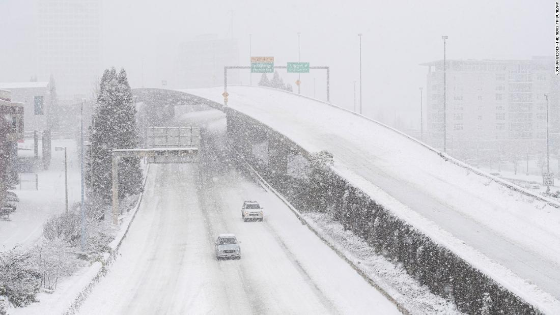 Cars drive along Interstate 705 as snow falls in Tacoma, Washington, on Saturday.