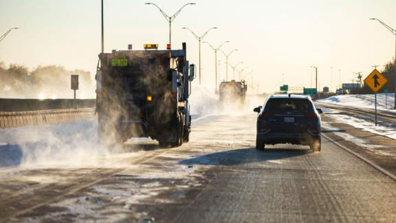 Snow plows clear a lane of I-30, Monday, Feb. 15, 2021, in Dallas. The Nashville Predators and the Dallas Stars NHL hockey game Monday was postponed at the request of Dallas Mayor Eric Johnson due to a shortage of electricity in the region. (AP Photo/Brandon Wade)