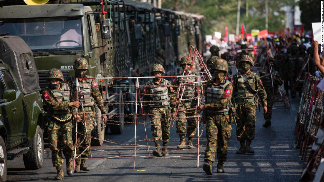 Soldiers carry barricades in Yangon on February 15.