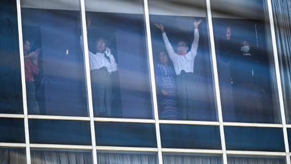 Elected members of Parliament wave to protesters in Yangon as police surround the headquarters of Suu Kyi's political party, the National League for Democracy, on February 15.