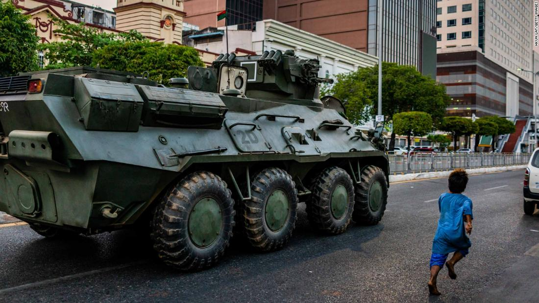 A child runs alongside an armored vehicle in Yangon on February 14.
