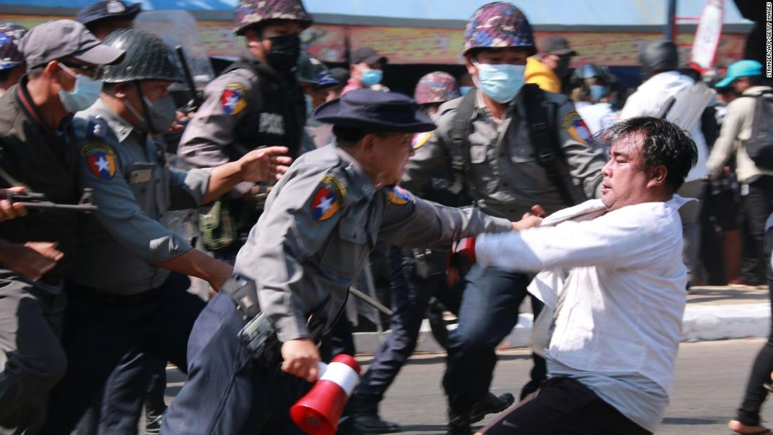 Police detain a protester during a demonstration in Mawlamyine on February 12.