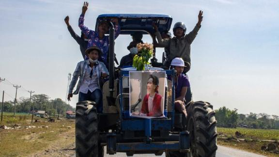 Farmers ride a tractor with a Suu Kyi poster during a demonstration in Thongwa on February 12.