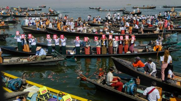 """People hold up letters that spell """"get out dictators"""" during a demonstration at Inle Lake on February 11."""
