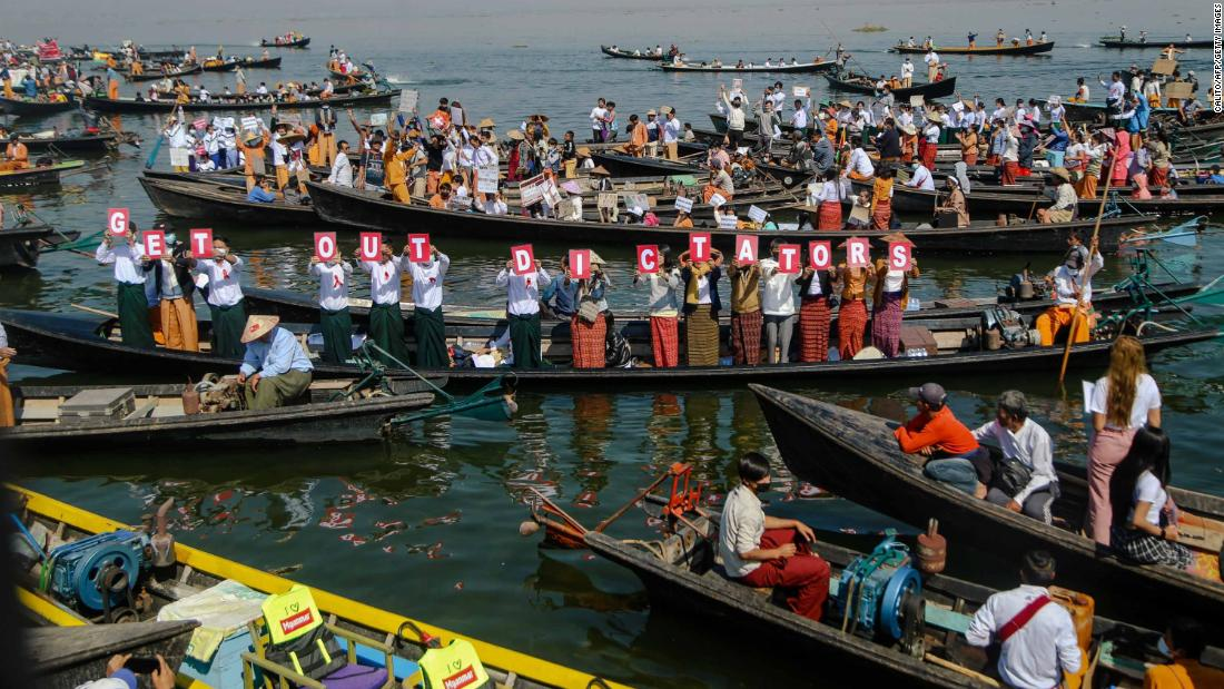 "People hold up letters that spell ""get out dictators"" during a demonstration at Inle Lake on February 11."