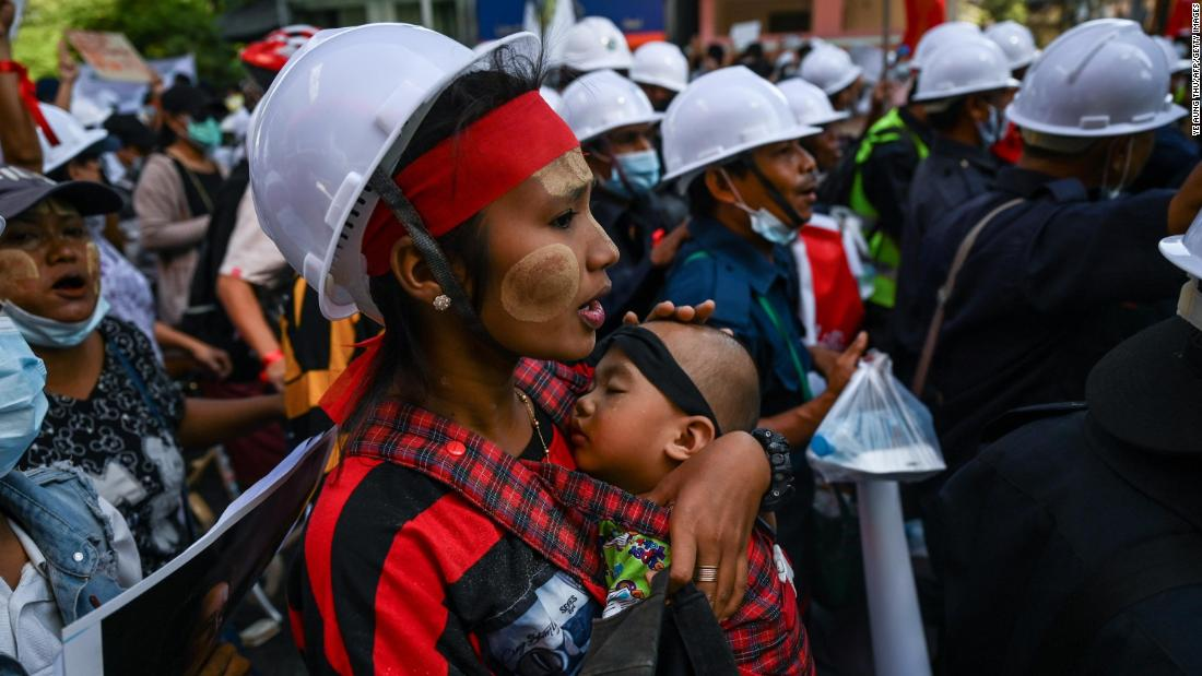 A protester carries a child during a march in Yangon on February 10.