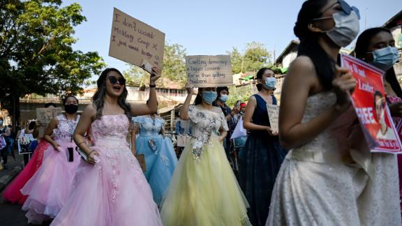 Women in wedding gowns holds up anti-coup placards in Yangon on February 10.