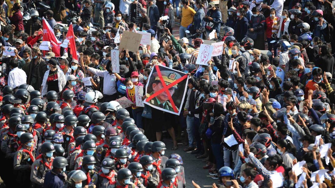 Protesters flash three-fingered salutes as they face rows of riot police in Naypyidaw on February 8.