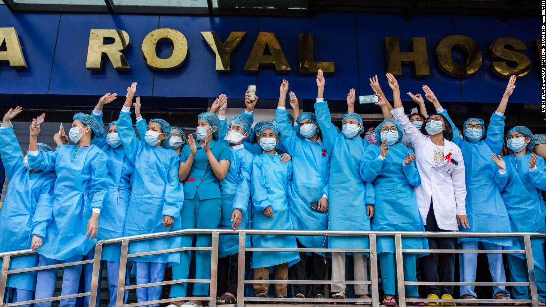 Hospital workers show three-finger salutes during a demonstration in Yangon on February 7.