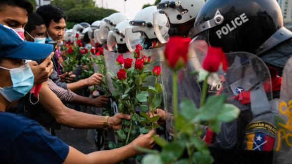 Protesters give roses to riot police in Yangon on February 6.