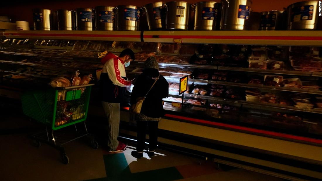 Customers use light from a cell phone as they shop for meat at a grocery store in Dallas on Tuesday. Even though the store lost power, it was open for cash-only sales.
