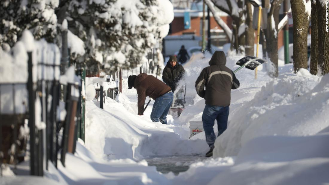 Residents clear snow from a sidewalk in Chicago on Tuesday.