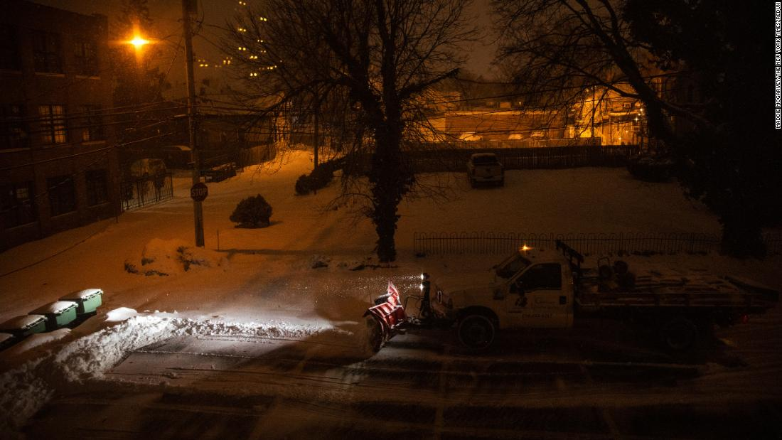 A snow plow clears a parking lot in Columbus, Ohio, early on Tuesday.