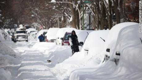 People work to dig out their cars along a residential street on Tuesday in Chicago, Illinois.
