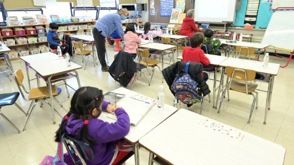 Binasa Musovic (left), an educational paraprofessional, and teacher Chris Frank (right), instruct blended learning students on the first day back to school, December 7, 2020, at Yung Wing School P.S. 124 in New York City.