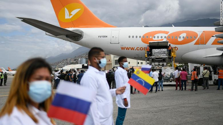 Healthcare workers hold national flags from Venezuela and Russia as workers unload a shipment of the Russian COVID-19 vaccine Sputnik V, at the Simon Bolivar International Airport in Maiquetia, Venezuela, Saturday, Feb. 13, 2021.