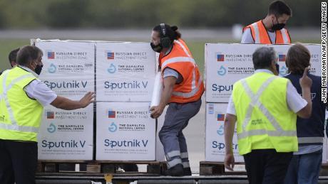12 फरवरी, 2021 को ब्यूनस आयर्स में एज़िज़ा अंतर्राष्ट्रीय हवाई अड्डे पर COVID -19 के खिलाफ स्पुतनिक वी वैक्सीन की खुराक के साथ हवाई अड्डे के श्रमिकों ने कंटेनर को उतार दिया।