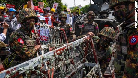Protesters hold banners and shout slogans while Myanmar military soldiers from the 77th Light Infantry Division place barbed wire barricades on February 15, 2021 in Yangon, Myanmar.