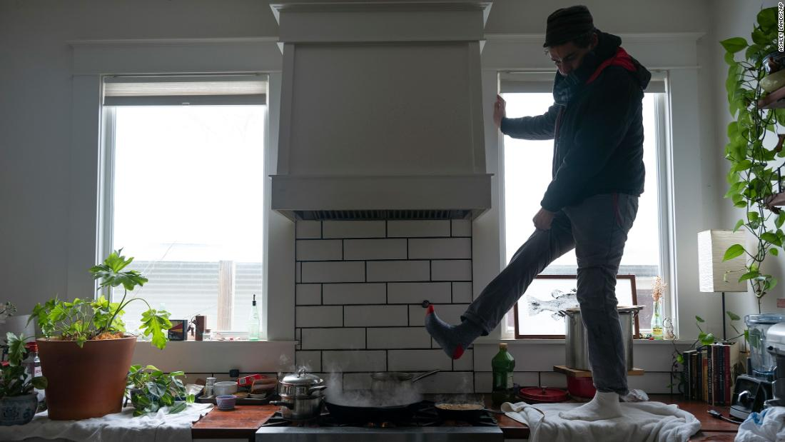 Jorge Sanhueza-Lyon stands on his kitchen counter to warm his feet over his gas stove in Austin.
