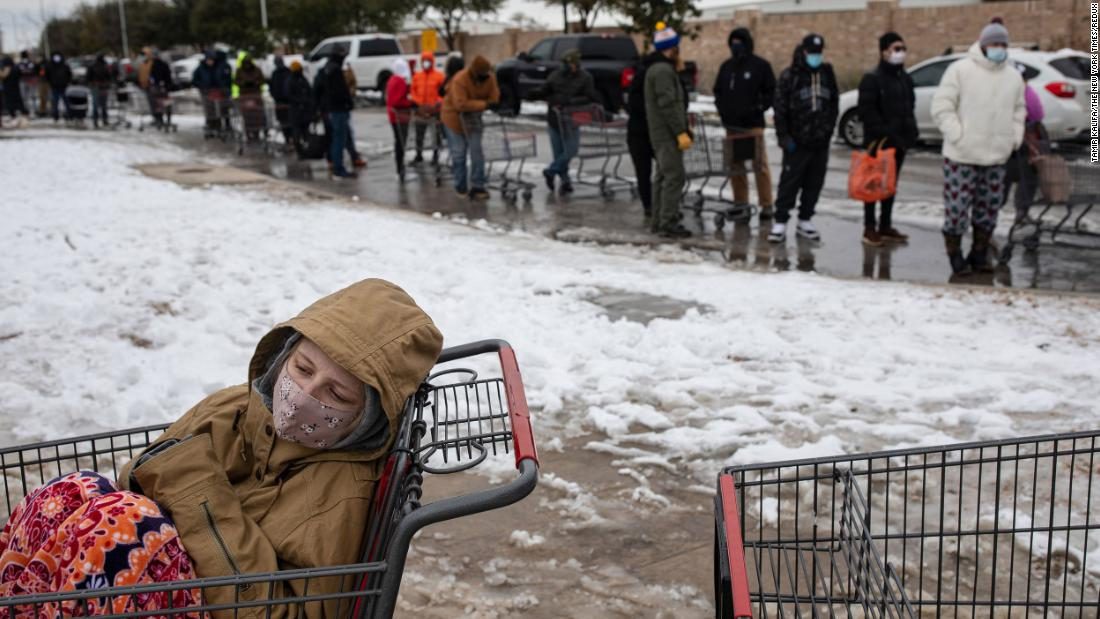 Camilla Swindle sits in a shopping cart as she and her boyfriend wait in a long line to enter a grocery store in Austin on Tuesday.