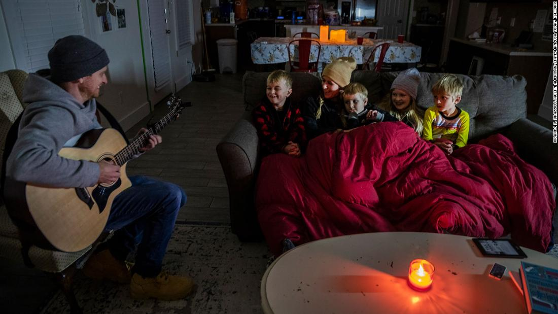 Brett Archibad entertains his family as they try to stay warm in their home in Pflugerville, Texas, on Tuesday.