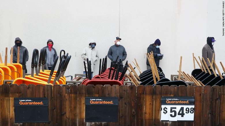 Customers wait outside a Home Depot in Pearland, Texas, to enter to buy needed supplies.