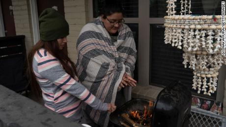 Karla Perez and Esperanza Gonzalez warm up by a barbecue grill during power outage caused by the winter storm on February 16.