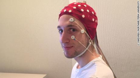 A study participant in a full EEG rig just before a sleep session in the lab. The electrodes on his face will detect the movement of his eyes as he sleeps.