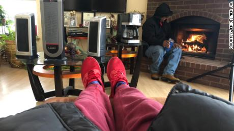 Eric Siner, Jr. warms his feet while his father sits by the fireplace after their neighbor hooked up their heaters to his generator.