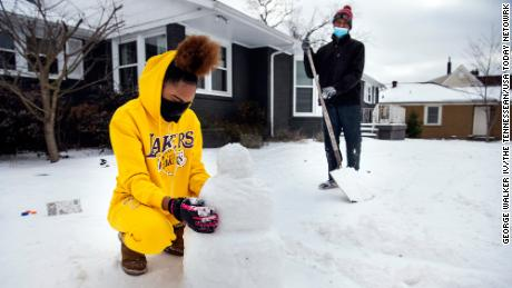 Madison Horton 15, builds a snowman in her front yard of her home in Nashville, Tennessee.