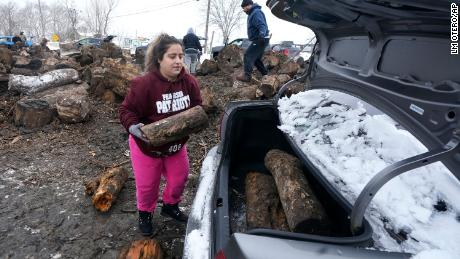 Sara Castillo loads firewood into her car Wednesday in Dallas.