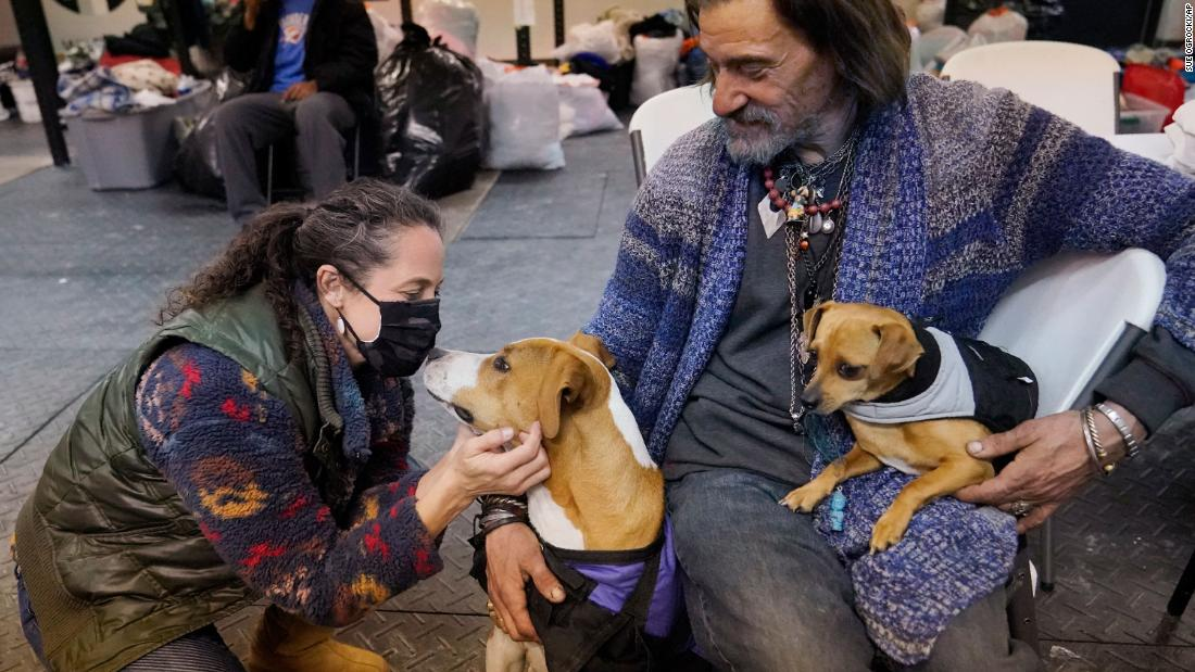 Kendra Clements visits dog owner Billy Madden -- with his dogs Leroy Brown and Underdog -- at Tribe Gym, an Oklahoma City gym that has been turned into a temporary homeless shelter.