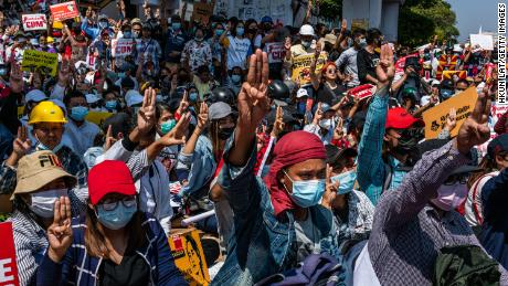 Protesters make three-fingered salutes and chant slogans during an anti-coup protest at Sule Square on February 17, 2021 in Yangon, Myanmar.