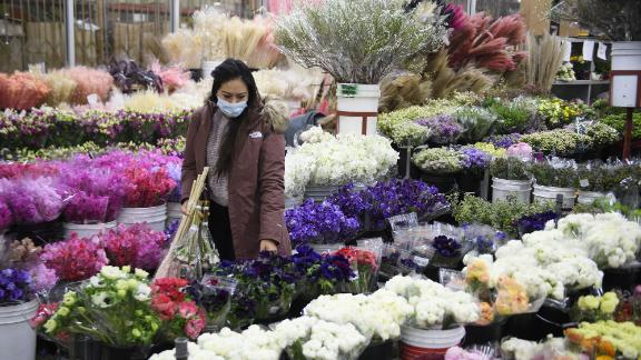 A customer wears a face mask while shopping for flowers displayed for sale from a wholesale merchant ahead of the Valentine's Day holiday at the Southern California Flower Market on February 12, 2021 in Los Angeles, California. - While some florists note an increased demand for socially distant gifts, the Covid-19 pandemic has impacted global supply chains and shut down most large events including weddings where flowers are popular. The Valentine's Day and Mother's Day holidays are historically the two busiest days of the year for floral businesses. (Photo by Patrick T. FALLON / AFP) (Photo by PATRICK T. FALLON/AFP via Getty Images)