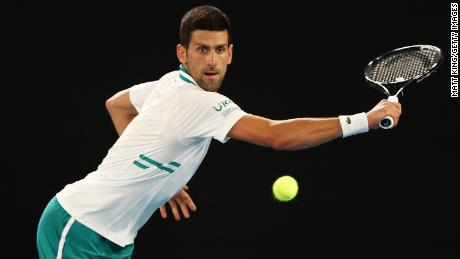 Djokovic plays a backhand against Karatsev.