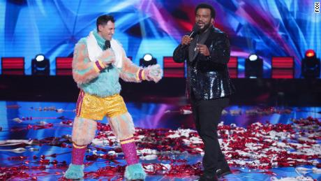 """THE MASKED SINGER: L-R: Maksim Chmerkovskiy and host Craig Robinson in the """"Road to the Finals -- Final Clues to the Mask!/ The Finale -- One Last Mask!"""" special two-hour season finale of THE MASKED DANCER airing Wednesday, Feb. 17 (8:00-10:00 PM ET/PT) on FOX.  © 2021 FOX Media LLC."""