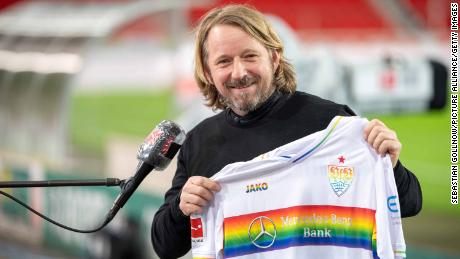 Sven Mislintat, sporting director for VfB Stuttgart, holds a jersey with the rainbow design in support of LGBTQ footballers.