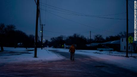 Charles Andrews, 57, walks home through his neighborhood in Waco, Texas as severe winter weather conditions over the last few days has forced road closures and power outages over the state on February 17, 2021. - Millions of people were still without power on February 17 in Texas, the oil and gas capital of the United States, and facing water shortages as an unusual winter storm pummeled the southeastern part of country. The National Weather Service (NWS) issued a winter storm warning for a swathe of the country ranging from east Texas to the East Coast state of Maryland. (Photo by Matthew Busch / AFP) (Photo by MATTHEW BUSCH/AFP via Getty Images)