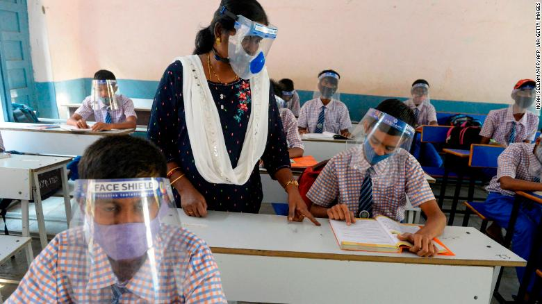 Students wearing face masks and face shields attend class in Hyderabad, India, on February 6, 2021.
