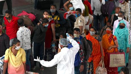 A health worker checks the body temperature of arriving passengers at a railway terminus in Mumbai on January 6, 2021.