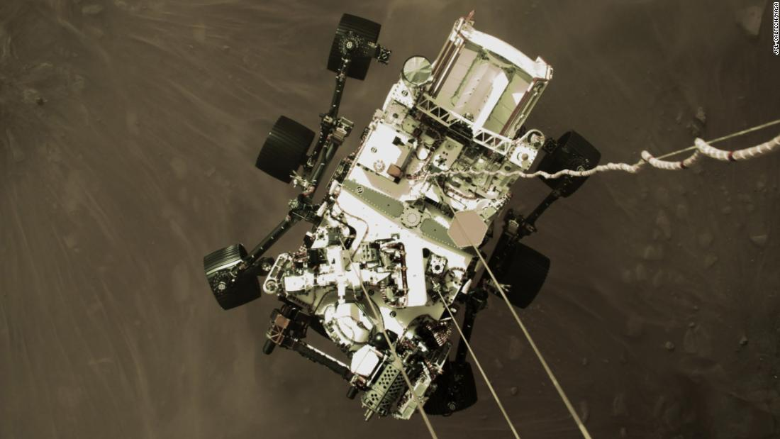 "This image, from a camera on Perseverance's ""jetpack"" during the spacecraft's descent stage, captures the rover in midair just before its wheels touched down. This perspective has never been seen before on previous missions."